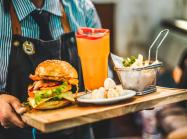 Restaurant employee serving burger with pitcher of juice.