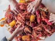 Hook and Reel customers grab seafood off a table.