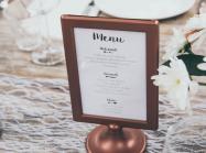 Menu-printed board with brown frame on table.