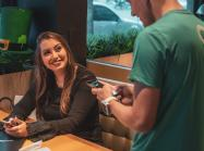 Restaurant employee talks to guest at a table.
