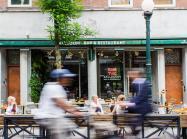 People bike by a restaurant outside.