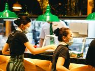 Two waitresses wearing masks inside a restaurant.