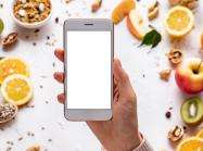 Female hands holding smartphone on healthy food background.