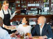 Waitress wearing face protective mask bringing ordered pizza to guests.