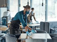 Busy young male waiters in protective workwear cleaning tables in restaurant.