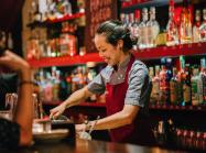 A woman cashes out a customer behind the bar of a restaurant.