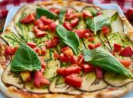 A pizza with basil and tomatoes.