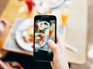 A person holds a phone and takes a picture of food.