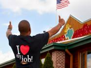A Texas Roadhouse employee gives the thumbs up outside a restaurant.