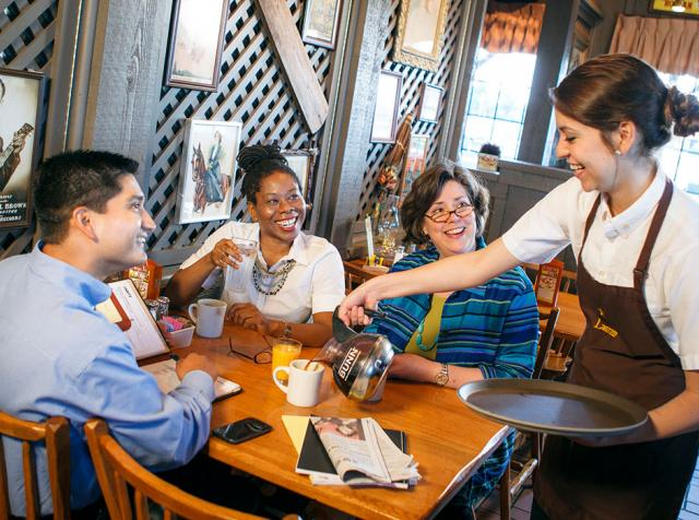 A Cracker Barrel waitress serves guests inside the restaurant.