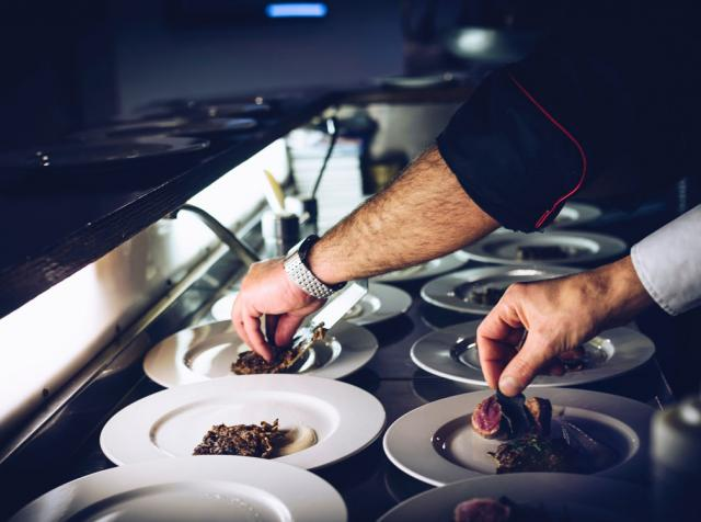 Two chefs plate food in a commercial restaurant kitchen.
