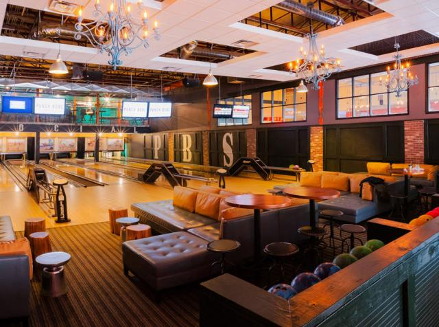 Inside a Punch Bowl Social restaurant, with bowling lanes and couches.
