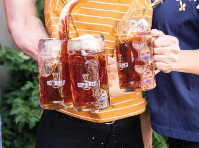 People holding steins of beer