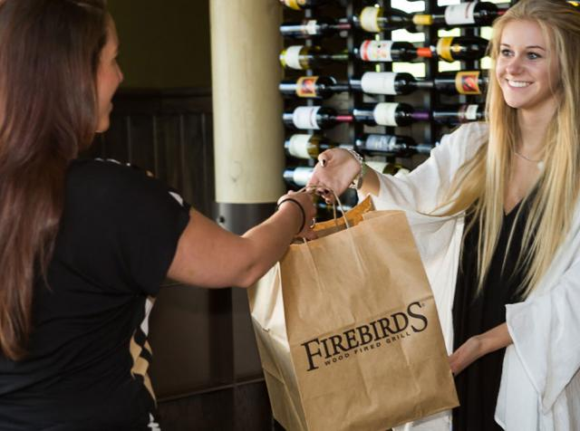 A Firebirds restaurant employee hands a bag of food to a customer.
