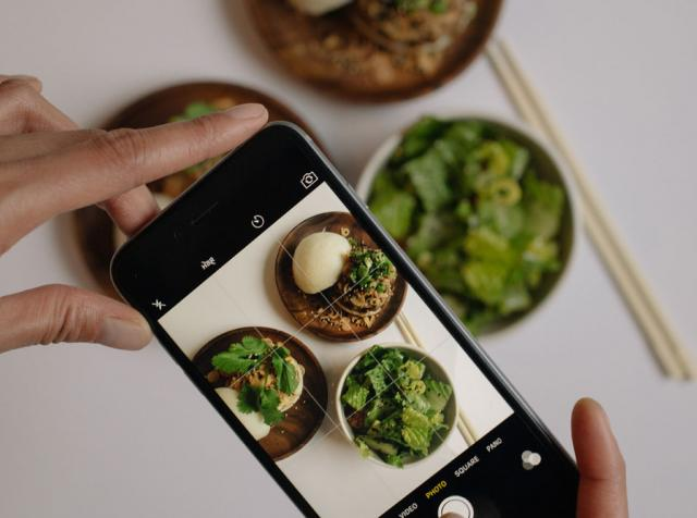 Person taking picture of vegetables with their mobile phone.