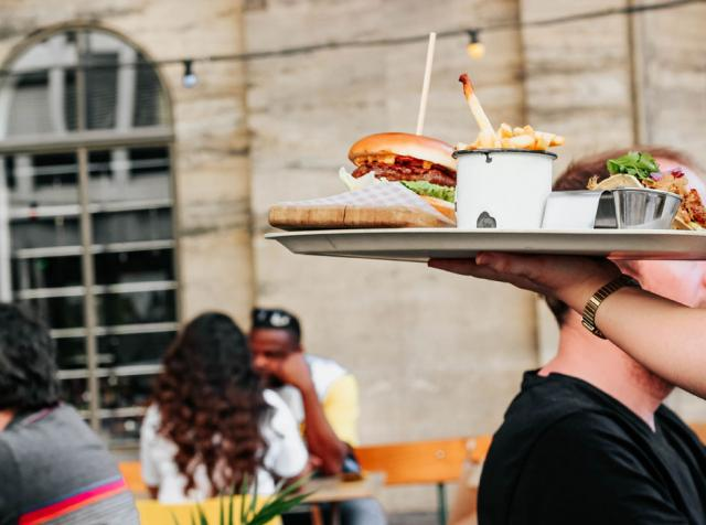 Hamburger on tray being served by person in white shirt.