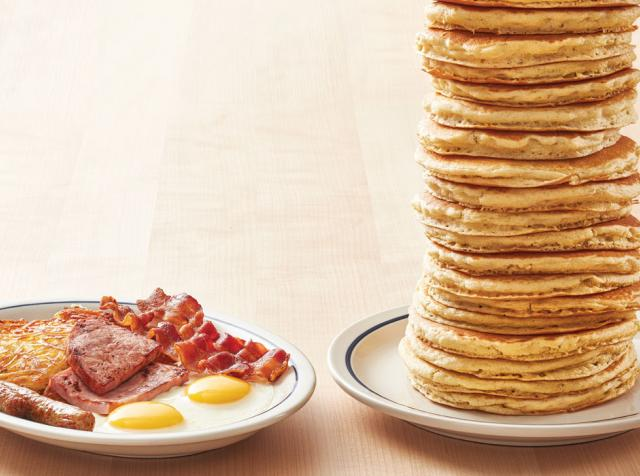 Stack of IHOP pancakes next to breakfast plate.