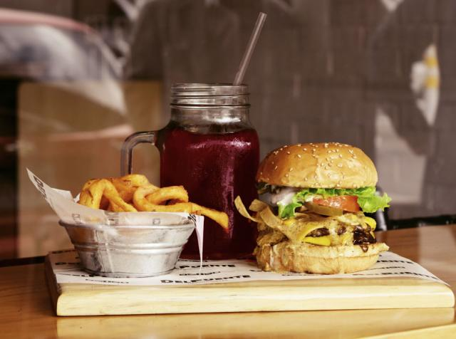 Burger and fries on a wooden plate.