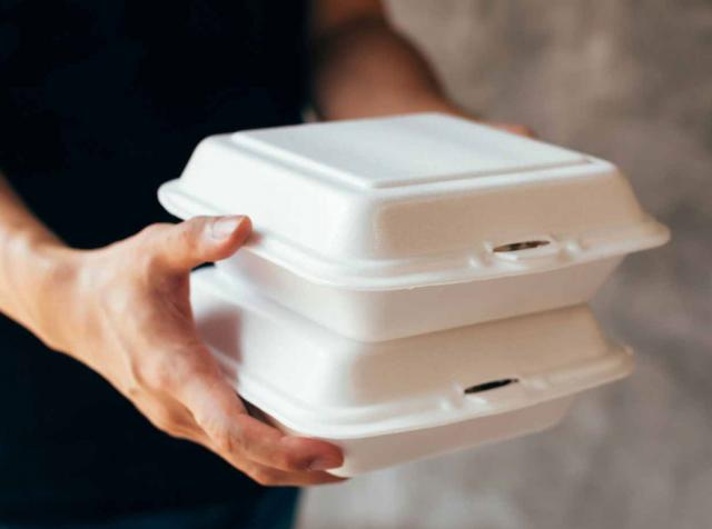 A restaurant customer carries two cartons of food.