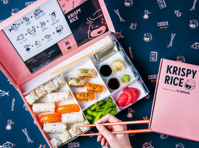 Box of sushi on a table.