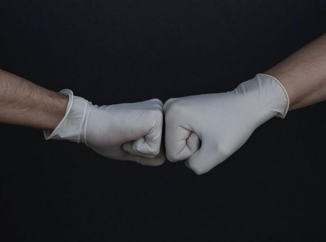 Two people wearing gloves doing a fist bump.