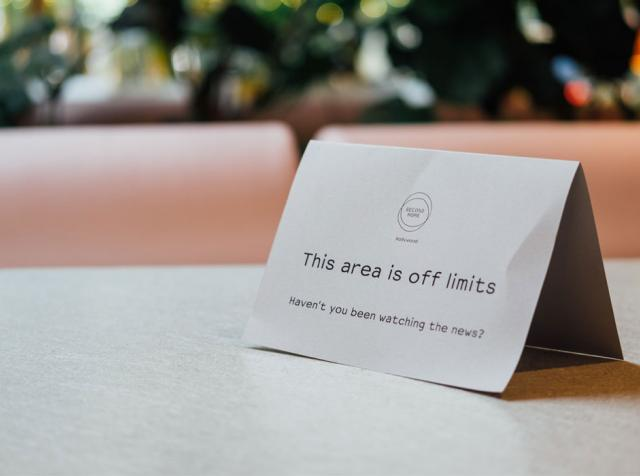 "A sign reading ""this area is off limits"" on a restaurant table."