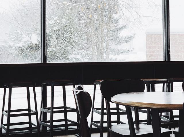 Snow falling outside a restaurant window.