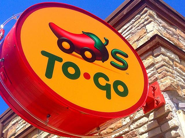 Chili's to-go signs hangs outside a restaurant. The brand is cutting its menu to improve operations.