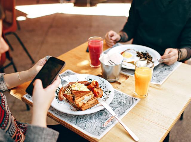 Woman uses a phone while eating breakfast with a friend.