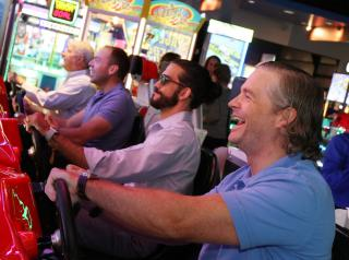 Adults play arcade games at Main Event.