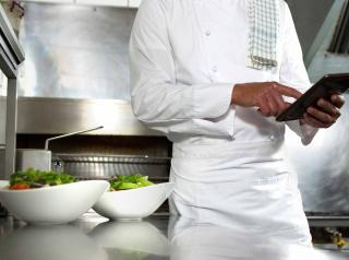 Chef using mobile phone in the kitchen.