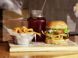 Cear glass mason jar, burger and fries on brown wooden board.