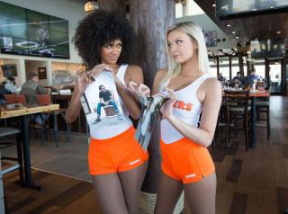 Hooters waitresses hold up photos.
