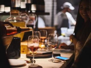 Customers drink wine at a table while dining at Barcelona Wine Bar.