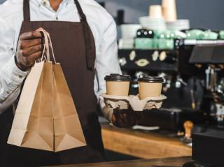 Restaurant employee hands coffee and a bag of food to customers.