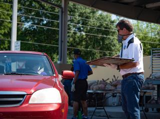 Feed the Need Florida employee giving a meal to someone in a car.