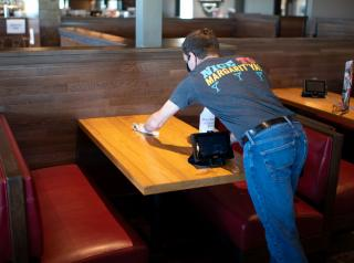 Chili's employee cleans a table inside the restaurant.