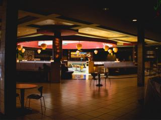 An empty food court with dimmed lights.