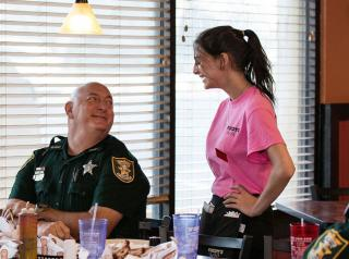 Police officer talks to a server at Woody's Bar-B-Q.