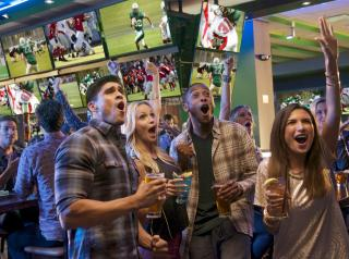 Dave  & Buster's customers watch sports on TV with drinks in their hands.
