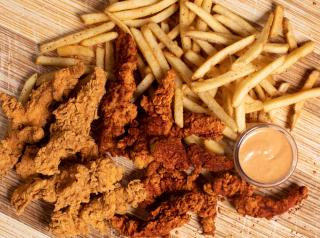 Chicken tenders, fries, and sauce on a wooden table.