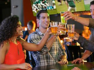 Four customers cheers beer glasses inside a Dave & Buster's with sports playing on TVs in the background.