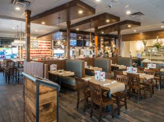Shoney's new restaurant design featuring wood flooring, community tables lit by modern light fixtures, and a full-service bar highlighted by red subway tile.