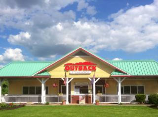 The exterior of an Outback restaurant with a blue sky behind.