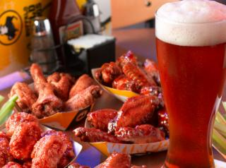 A tall glass of frosty beer next to wings at Buffalo Wild Wings.