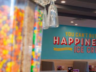 "A sign reads, ""you can't buy happiness but you can buy ice cream,"" inside a Friendly's restaurant."
