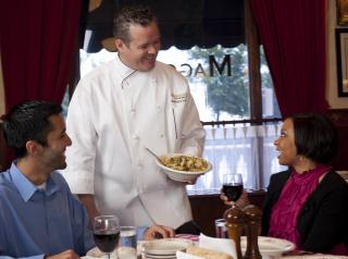 A waiter serves food at Maggiano's Little Italy.