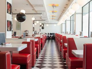 Booths in a diner with white and black checkerboard tiles.