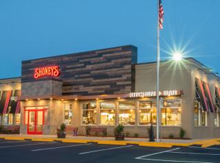 Shoney's exterior design exterior design showcases natural wood and stone siding, elongated black awnings, and a red backlit Shoney's logo.