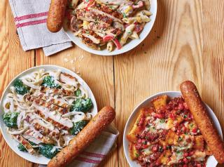 Three plates of Applebee's new Neighborhood Pasta bowls and breadsticks.